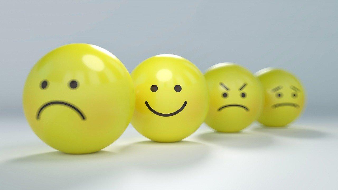 Quatro bolinhas amarelas representando os sentimentos humanos: tristeza, alegria, raiva e decepção.