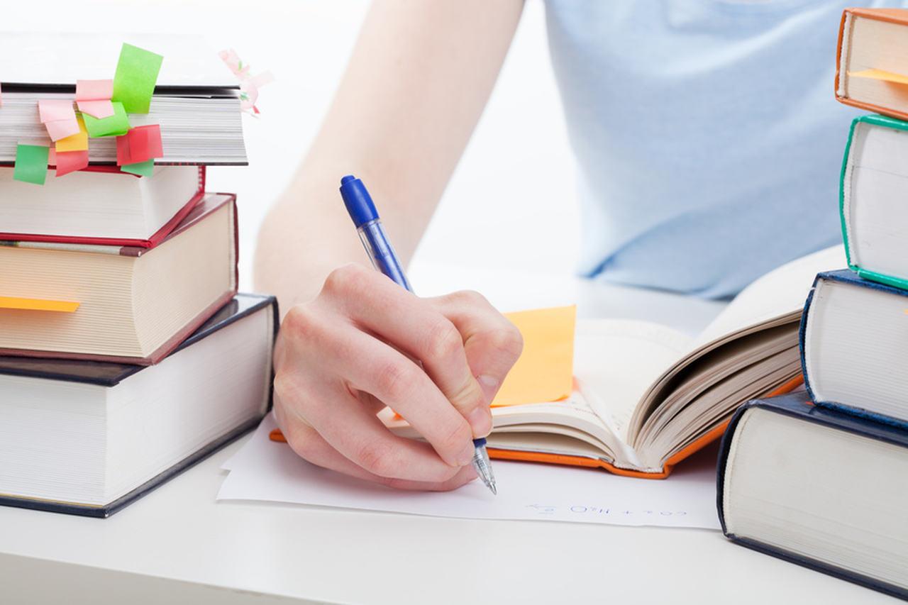 como-se-organizar-para-estudar - mão segurando caneta em meio a livros