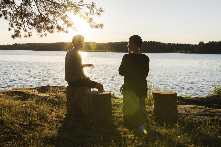 Dois homens sentados à beira de um lago conversando.