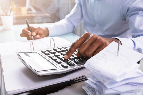 perfil-estudante-ciencias-contabeis - homem apertando botao de calculadora e escrevendo em um papel