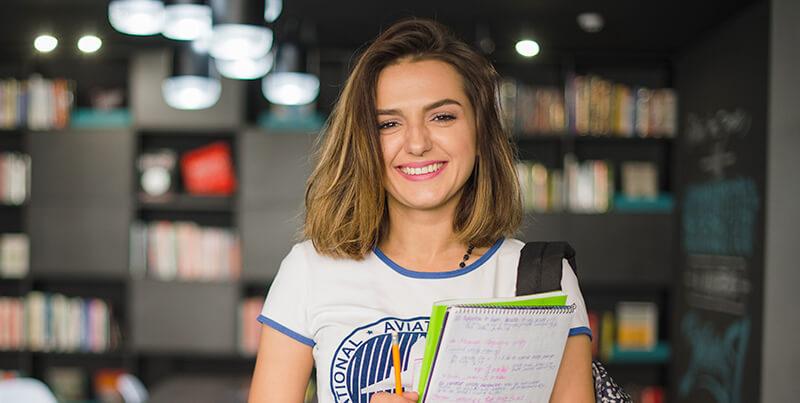 Aluna da graduação EAD sorrindo segurando cadernos.